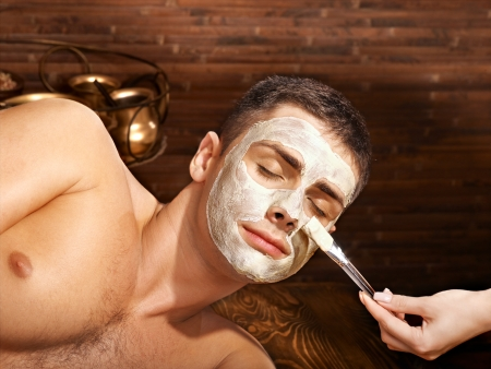 Man with clay facial mask in beauty spa. Stock Photo - 22847100
