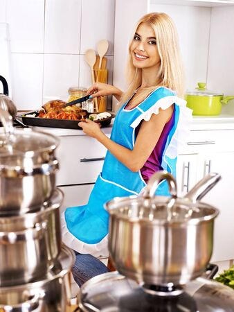 Young woman cooking chicken at kitchen. photo