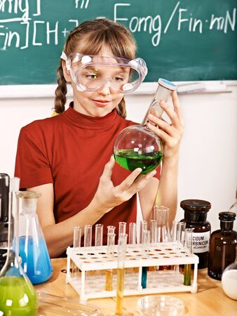 Child holding flask in chemistry class. photo