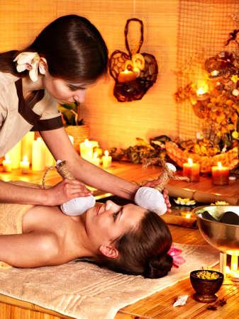 herbal massage ball: Young woman getting facial herbal massage ball.