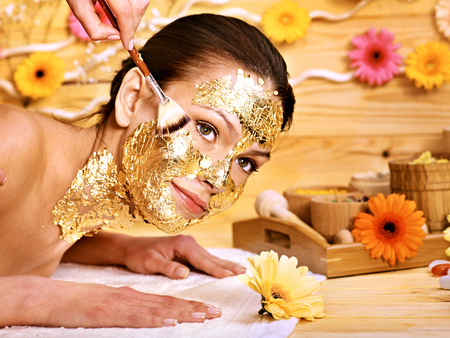 Woman getting  gold facial mask. photo