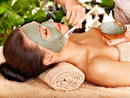 Beautiful woman having clay facial mask apply by beautician. photo