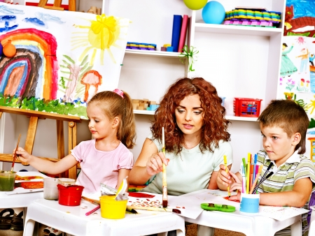 nursery school: Child with mother painting . Child care.