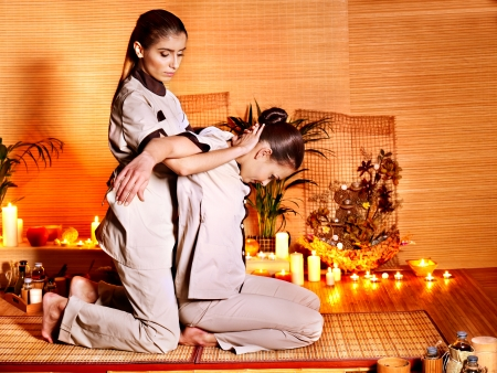 Therapist giving Thai stretching massage to woman. Imagens