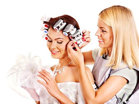 Woman with hair curlers on head wear in wedding dress . photo
