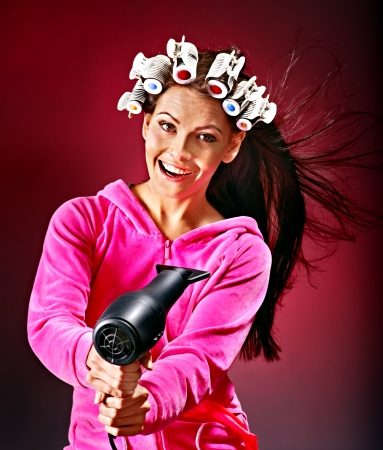 Happy woman wear hair curlers holding  hairdryer. photo