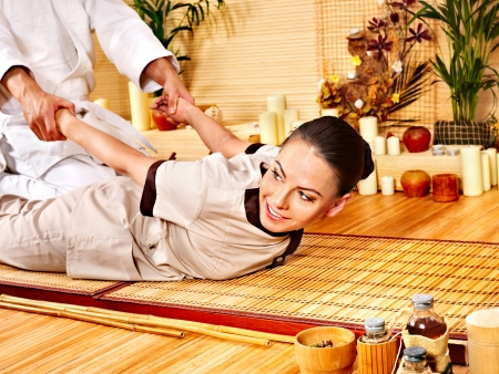 thai massage: Man getting bamboo massage. Female therapist. Stock Photo