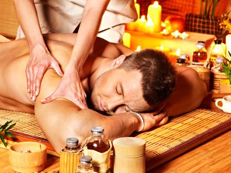 Man getting massage in bamboo spa. Female therapist. photo
