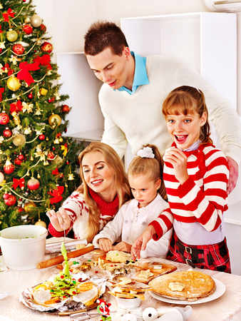 Happy family with children rolling bakery in Christmas kitchen. photo