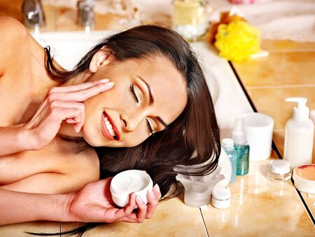 Woman applying moisturizer at bathroom. photo