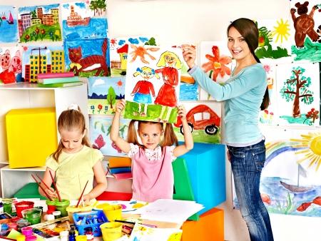 Happy children  with teacher at school.