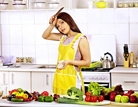 Unhappy tired woman preparing food at kitchen. photo