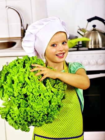 Child holding vegetable at kitchen. Stock Photo - 23356942