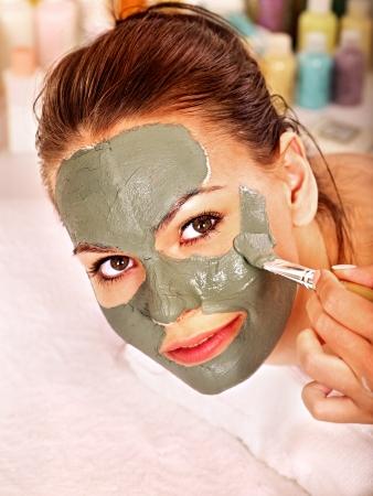 beauty wellness: Vrouw met klei gezichtsmasker in beauty spa.
