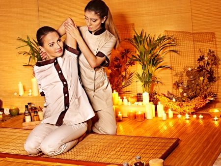 thailand bamboo: Therapist giving Thai stretching massage to woman. Stock Photo
