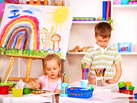 Child painting at easel in school. Teacher help. photo