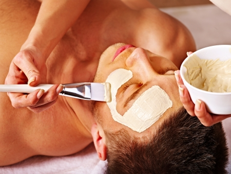 spa mud: Man with clay facial mask in beauty spa.