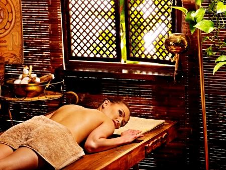 panchakarma: Woman having Ayurveda massage with herbal ball.