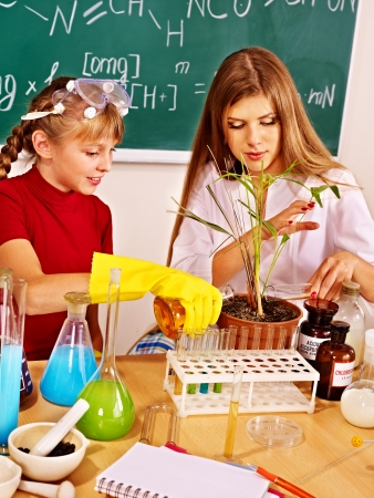 Child and teacher holding flask in chemistry class. photo
