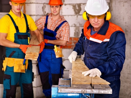 millwright: Happy group people  builder with circular saw.
