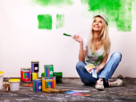painters: Happy woman paint wall at home.