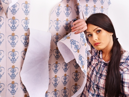 Tired woman glues wallpaper at home. photo