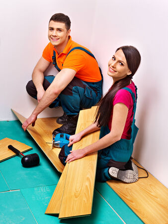 laminate flooring: Happy family laying parquet at home. Stock Photo