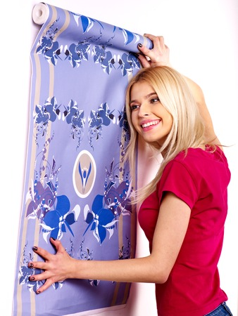Happy woman glues wallpaper at home. photo