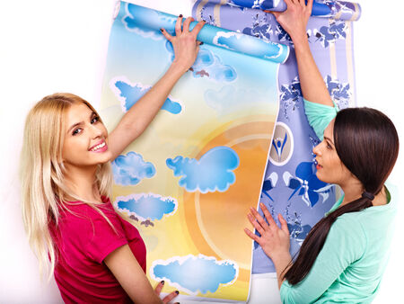 Happy women glues wallpaper at home. photo