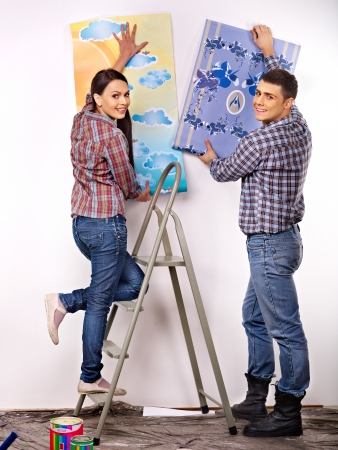Happy family glues wallpaper at home. photo
