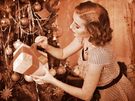 Woman receiving gifts under Christmas tree. Black and white retro. Stock Photo - 24177245