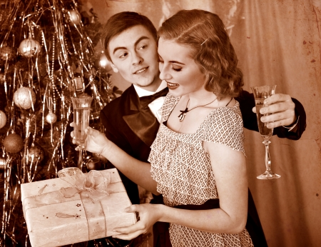 Couple on party near Christmas tree. Black and white retro. photo