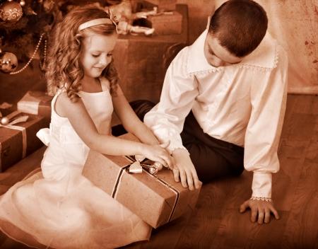 vistiendose: Los niños reciben los regalos bajo el árbol de Navidad. En blanco y negro retro. Foto de archivo