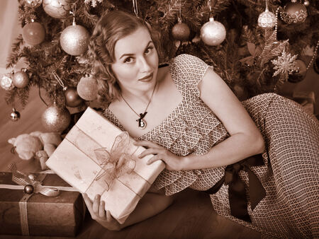Woman receiving gifts under Christmas tree. Black and white retro. Stock Photo - 24177250