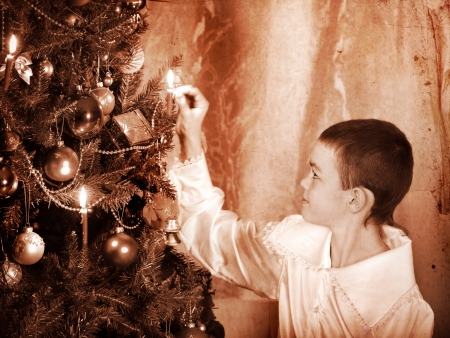 Boy lights candles on  Christmas tree. Black and white retro. Stock Photo - 24177221