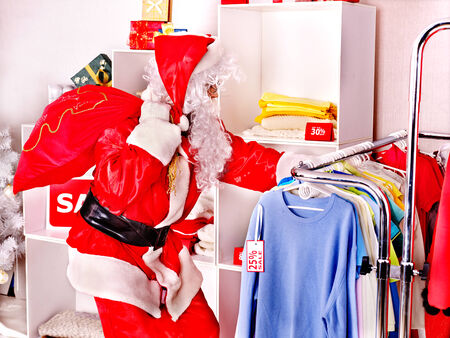 coathanger: Santa Claus in clothing store. Christmas sale.