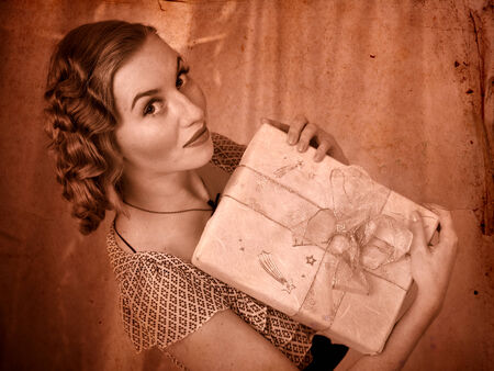 Woman holding gift box. Black and white retro. photo