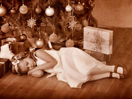 Child sleeping near Christmas tree. Black and white retro. photo