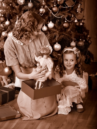 Child with mother receiving gifts under Christmas tree. Black and white retro. photo