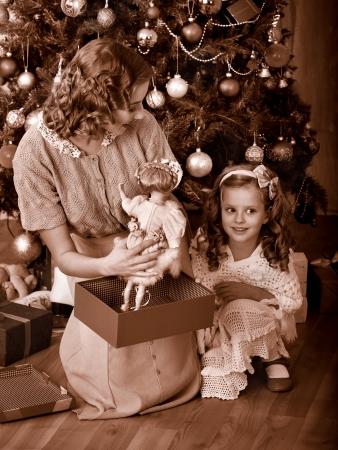 ni�os vistiendose: Ni�o con la madre de recibir regalos bajo el �rbol de Navidad. En blanco y negro retro. Foto de archivo