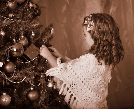 Little girl lights candles on  Christmas tree. Black and white retro. photo