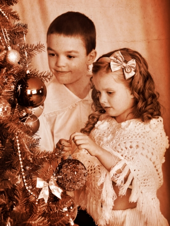 Child decorate on Christmas tree. Black and white retro. photo