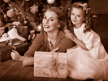 Child with mother receiving near Christmas tree. Black and white retro. Stock Photo - 24177081