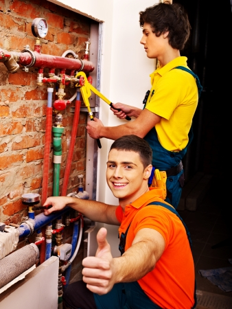 Men builder fixing heating system with special tool. photo