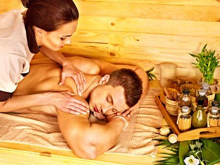 female therapist: Man getting massage in bamboo spa. Female therapist.