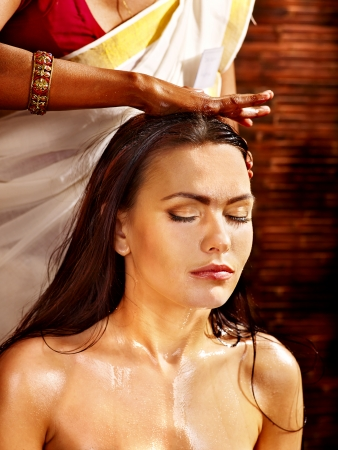 treatment: Young woman having head ayurveda spa treatment.