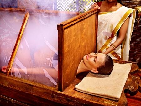 Woman having Ayurvedic sauna treatment.