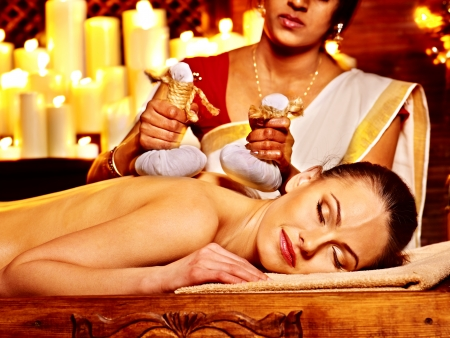 Woman having ayurvedic massage with pouch of rice. photo