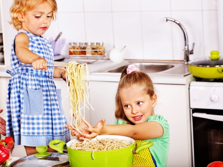 Children  eating spaghetti at kitchen. photo