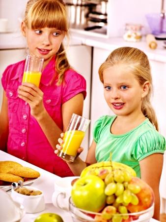 niños desayunando: Desayuno feliz de los niños en la cocina. Foto de archivo
